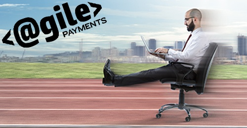 man speeding down track in office chair with laptop on his lap