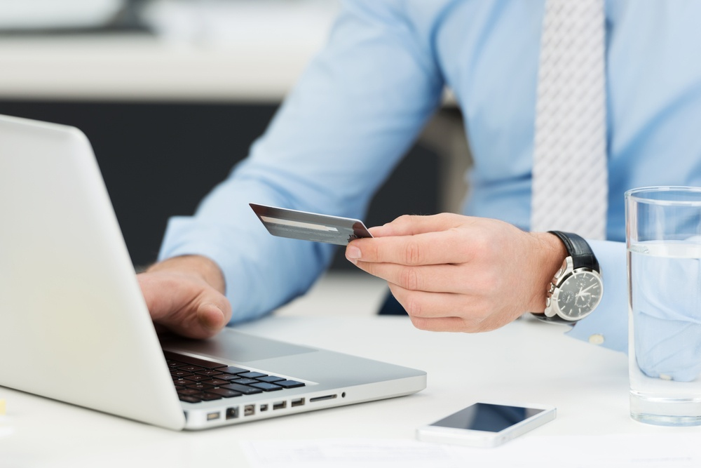 Businessman doing online banking, making a payment or purchasing goods on the internet entering his credit card details on a laptop, close up view of his hands.jpeg